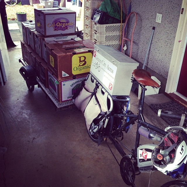 A delivery bike loaded up up and ready to head out on a delivery.
